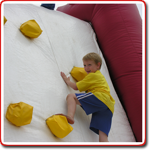 kid on inflatable rock wall
